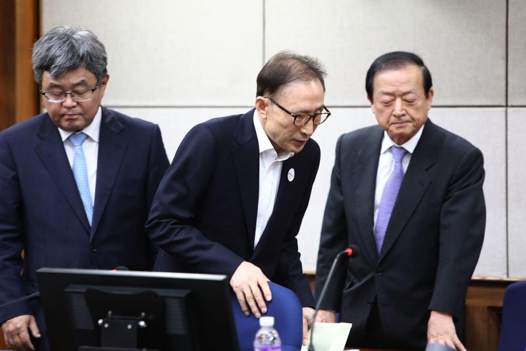 南韓前總統李明博(中)涉貪案終審判決宣判,李明博被判處有期徒刑17年。圖為2018年5月23日出席首次審判的情景。(Chung Sung-Jun/Getty Images)