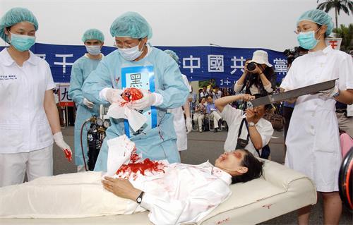 二零零六年四月二十三日,台灣法輪功學員在台北演示中共強摘中國法輪功學員器官的行動劇。(大紀元)