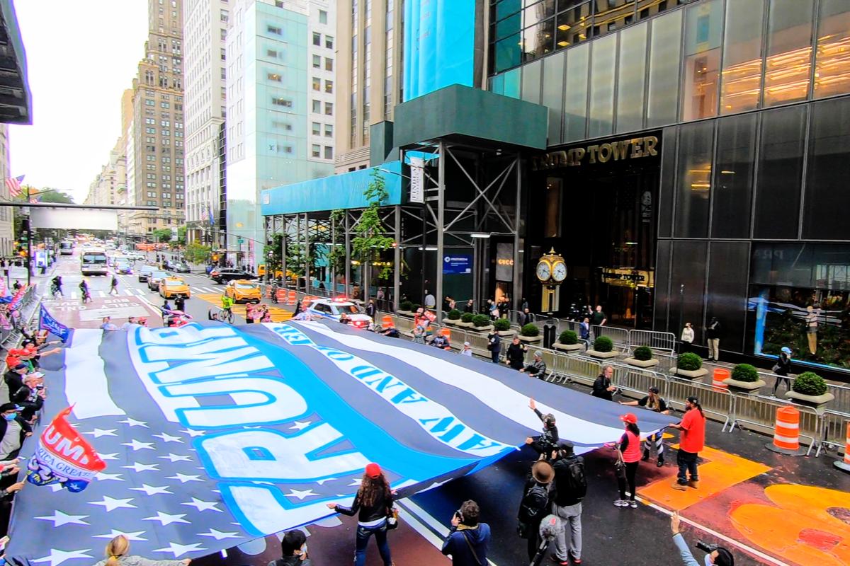 2020年10月13日,紐約市支持特朗普總統連任的民眾,合力在特朗普大廈前舉起一面巨幅黑白相間、中間有藍色條紋的美國國旗。(宋昇樺/大紀元)