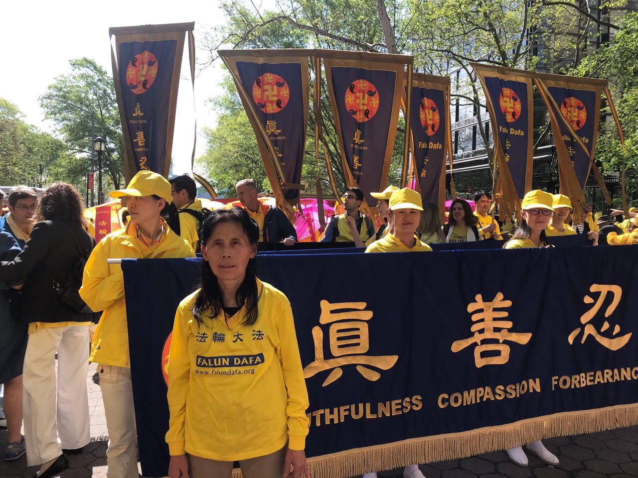 2019年5月16日,旅美大法弟子朱萍在紐約「慶祝世界法輪大法日」大遊行中,在「真善忍」條幅前留影。(李桂秀/大紀元)
