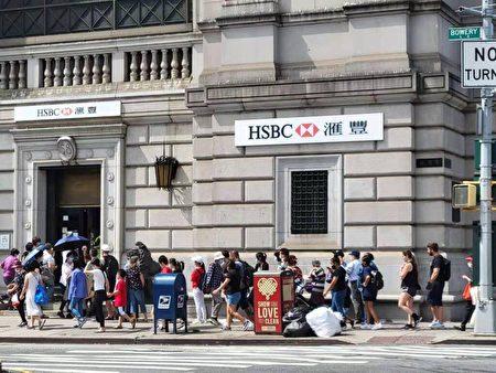 近日,紐約唐人街滙豐銀行(HSBC)門外,收到通知的滙豐客戶排長龍將保險箱內的東西搬出來。(讀者提供)