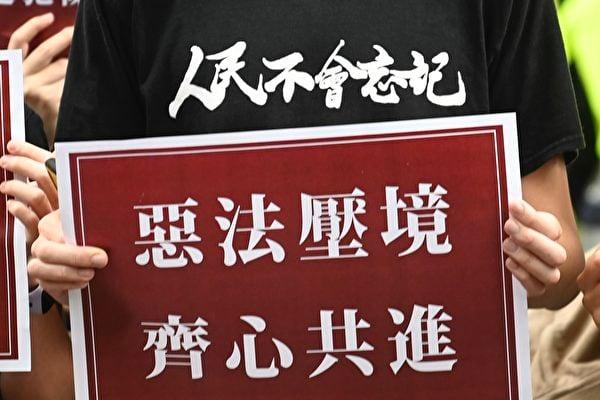 圖為香港民眾2020年7月1日上街抗議中共強行通過港版國安法,民眾手持「惡法壓境、齊心共進」的展板。(Sam Yeh/AFP)