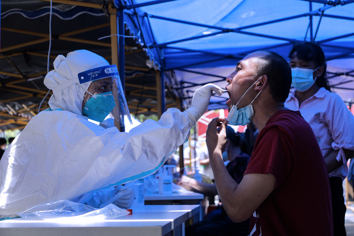 廣州市本輪疫情持續發酵,廣州全市核酸大排查中又發現陽性病例。圖為5月30日,廣州市民做核酸檢測。(STR/AFP via Getty Images)
