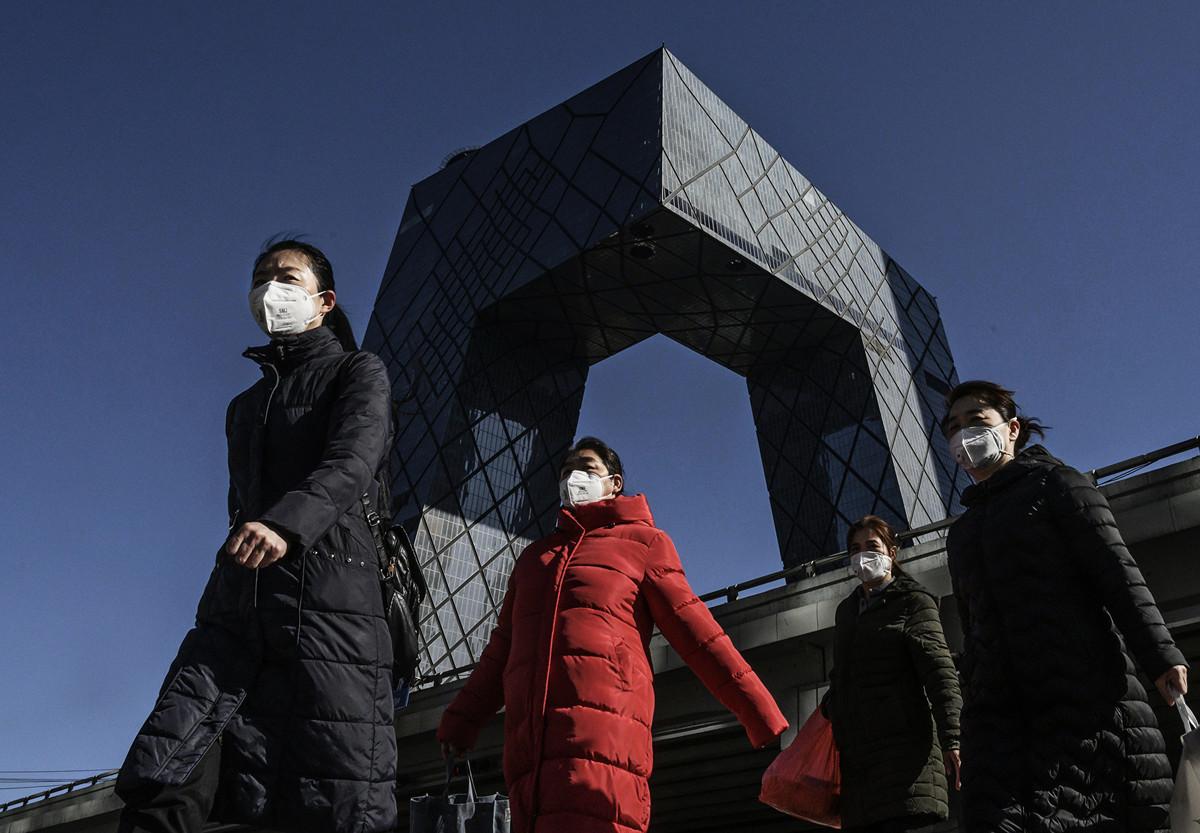 圖為2月17日帶著口罩的路人經過北京央視大樓。(Getty Images)