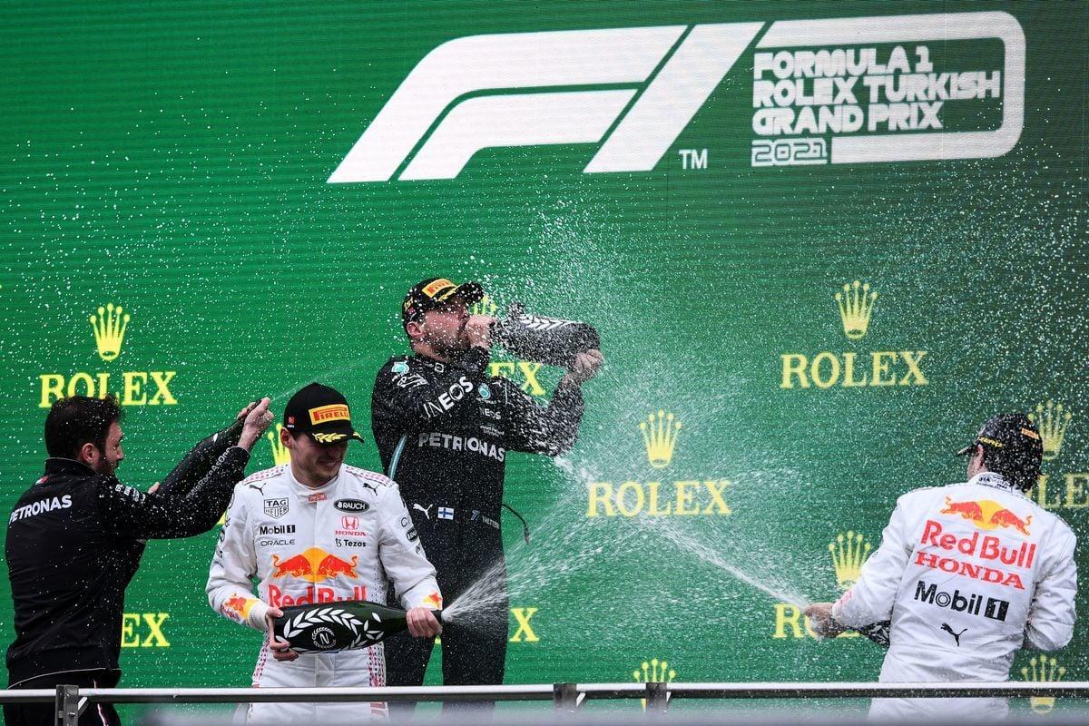 當地時間10月10日,F1大獎賽土耳其站,博塔斯(左三)奪得生涯第10個分站冠軍;紅牛雙雄維斯塔潘(左二)和佩雷茲(右一)分列第二、第三位。圖為三人在頒獎禮上互噴香檳慶祝。(OZAN KOSE/AFP via Getty Images)