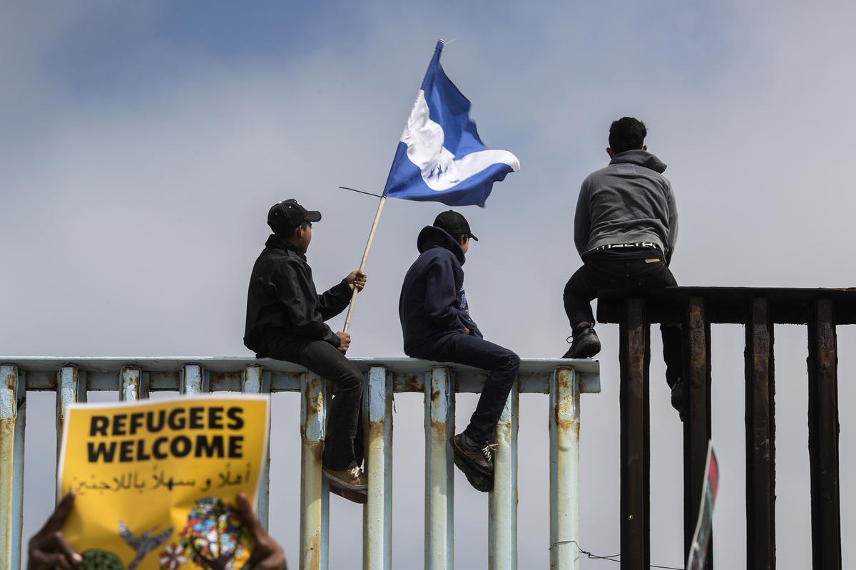 圖為2018年4月29日抵達墨西哥蒂華納的前一波中美洲大篷車成員,手持洪都拉斯國旗爬上美墨邊境一處圍欄,遠眺美國,他們希望能進入美國尋求政治庇護。(David McNew/Getty Images)