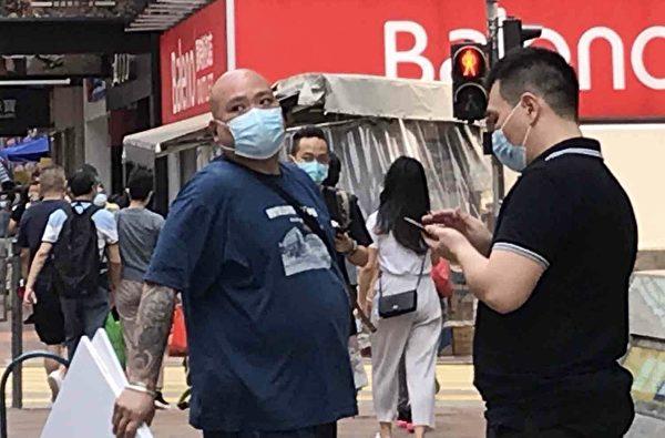 4月2日,2男1女在被損毀的香港旺角亞皆老街法輪功真相點旁邊架起污衊法輪功的橫幅,其中一男子是光頭,身上可見有紋身。(法輪功學員周小姐提供)