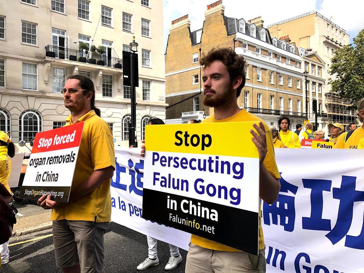 斯洛伐克法輪功學員Dalebor(右)和父親(左)在倫敦參加反迫害遊行。(邵燕/大紀元)