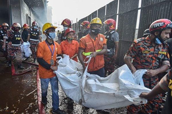 圖為消防和救援人員抬著找到的屍體。(Photo by MUNIR UZ ZAMAN/AFP via Getty Images)