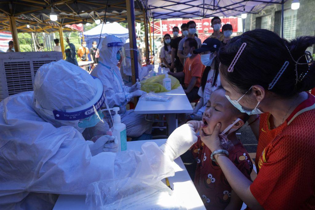 這張攝於2021年5月30日的照片顯示,一名兒童(右二)在中國廣東省廣州市接受COVID-19冠狀病毒核酸檢測。(Photo by STR/AFP via Getty Images)