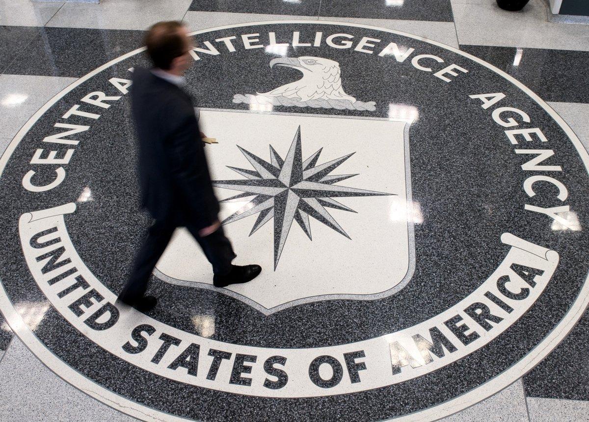 圖為2008年8月14日,一名男子在CIA總部的大廳越過地面上的logo。(SAUL LOEB/AFP via Getty Images)