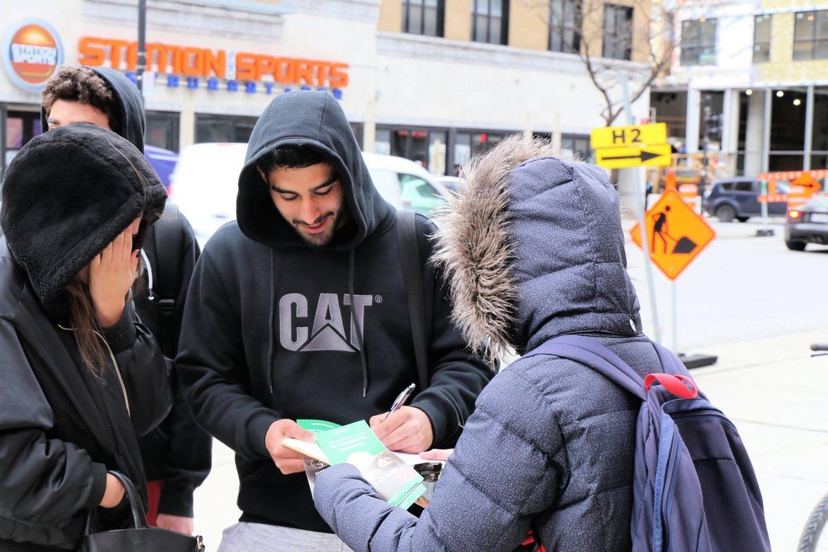 在4月20日的抗議活動期間,民眾在法輪功反迫害的徵簽信上簽字。(大紀元)