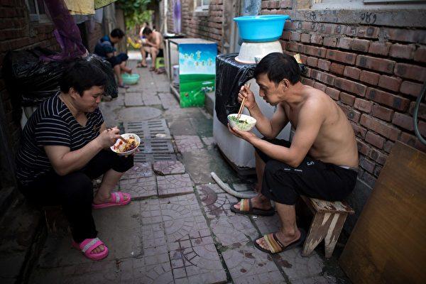 2017年8月17日,北京郊區一個農民工社區的街道上,人們正坐在屋外吃晚飯。(Nicolas Asfouri/AFP/Getty Images)
