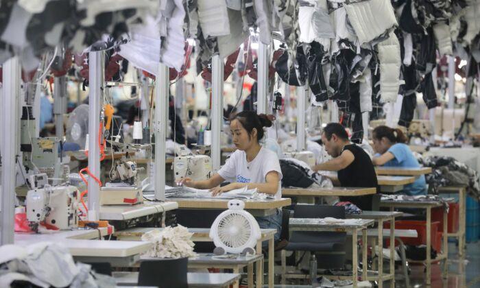 2019年9月24日,中國江蘇省南通市的中國服裝品牌波司登的一家工廠裏,工人正在縫製羽絨服。(STR/AFP/Getty Images)