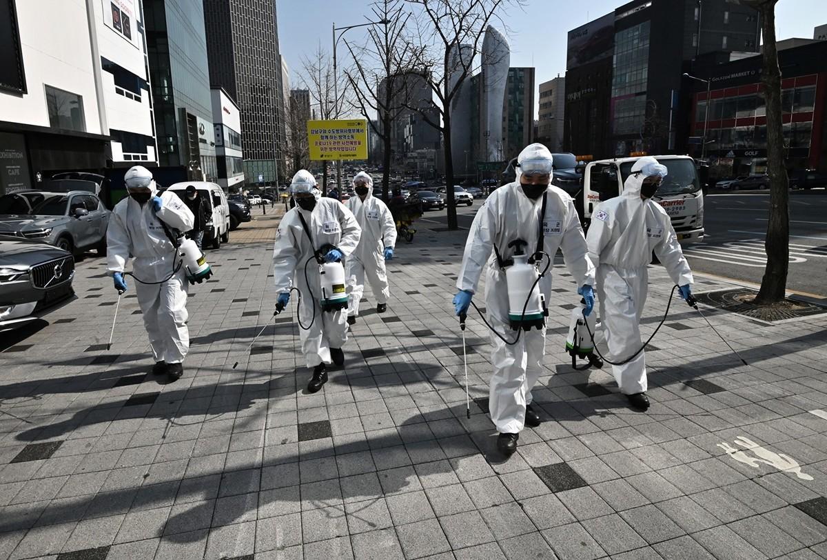 中共肺炎疫情爆發初期,南韓政府屈尊中共而未限制中國人入境,致使南韓疫情嚴重。圖為3月6日南韓士兵穿著防護裝備在首爾街上噴霧消毒劑。(Jung Yeon-je/AFP)