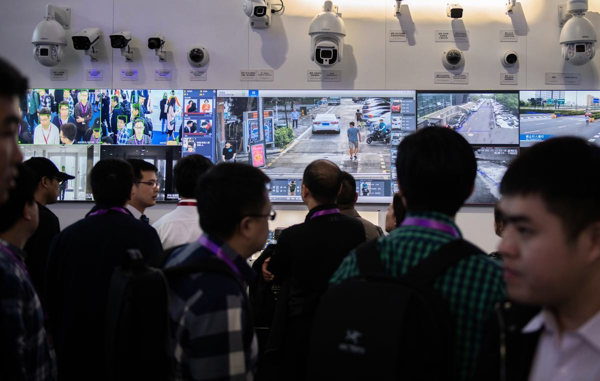 圖為2018年10月24日,在北京中國國際展覽中心舉行的第十四屆中國國際公共安全與安保展覽會上,參觀者在觀看採用人臉識別技術的AI(人工智能)安防錄像頭。(NICOL ASFOURI/AFP via Getty Images)