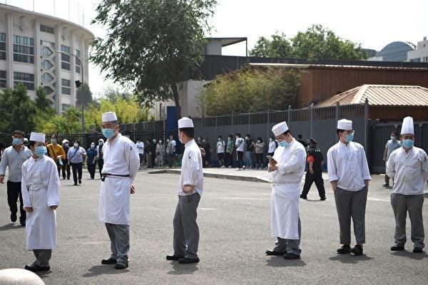 北京新發地疫情擴散,多家餐館發生群聚性感染,食客也暴露在危險中。圖為6月18日北京一家餐館廚師排隊做核酸檢測。 (NOEL CELIS/AFP via Getty Images)