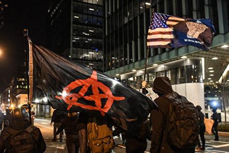 2020年12月12日,華盛頓特區舉行的抗議活動中,安提法組織的成員手持無政府主義和「黑人的命也是命」(BLM)旗幟。 (Stephanie Keith/Getty Images)