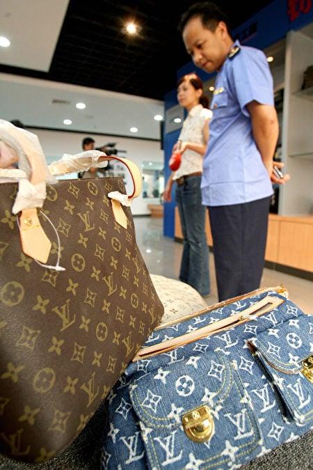 2007年6月12日,在北京工商局內,參觀者正在瀏覽展出的假冒路易威登(LV)手袋。在盜版問題上,中國也面臨越來越多的批評。4月時,美國就假冒奢侈品和DVD,向世界貿易組織提起訴訟。(Teh Eng Koon/AFP via Getty Images)