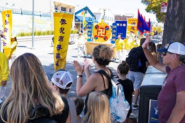 5月8日,美國三藩市部份法輪功學員在漁人碼頭旅遊景點遊行,恭祝師父華誕,慶祝「世界法輪大法日」。許多遊客駐足觀看。(周容/大紀元)