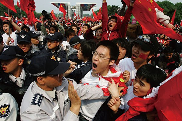 2008年4月27日,被中共組織來迎接中國奧運火炬接力的中國留學生激憤地對著南韓人權活動家咆哮。(Getty Images)