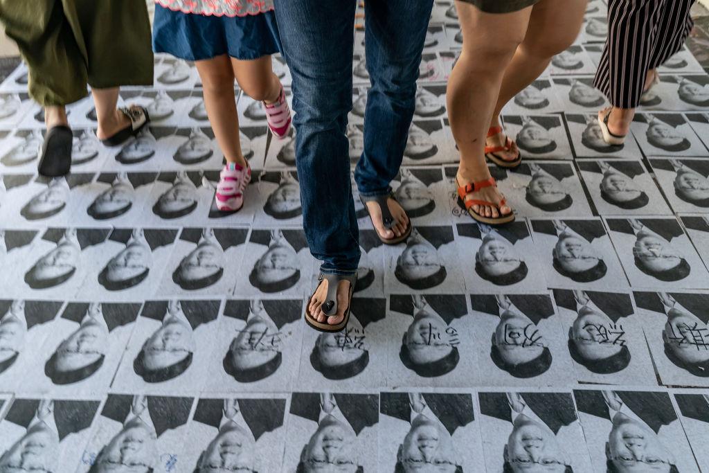 圖為何君堯照片被鋪在地上任人踩,成為當地一景。(Anthony Kwan/AFP/Getty Images)