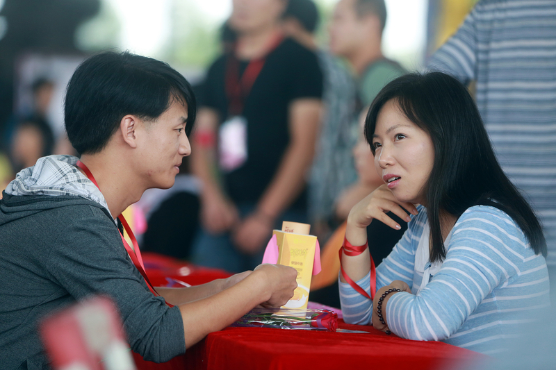 中國單身成年人口已超過2.2億人,許多單身人士選擇晚婚或不婚。圖為一對青年男女在廣東東莞的大型相親活動中聊天。(STR / AFP)