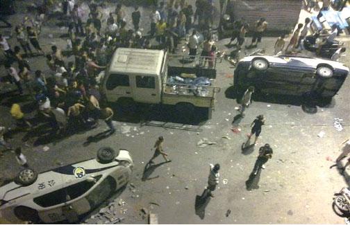圖為2011年6月12日,廣州新塘鎮發生大規模抗暴事件,抗議群眾推翻警車。起因是由於城管大隊對小攤販主人暴打致死,又對其懷孕妻子拳打腳踢,從而激起民憤。(Getty Images)