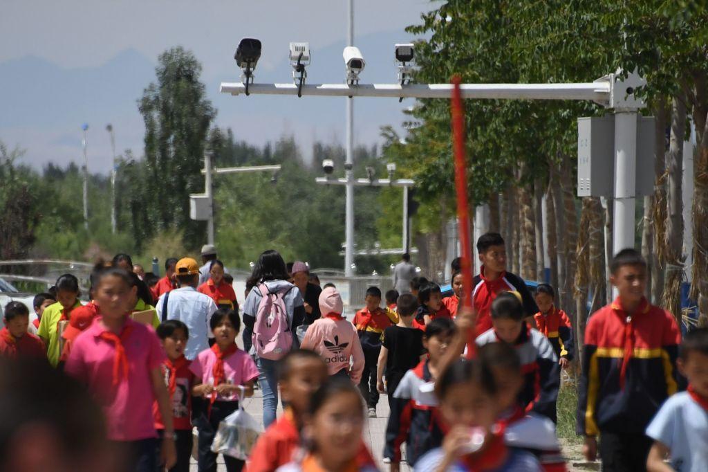 海外媒體聯合調查發現,中共邊檢人員在遊客手機上秘密安裝監控應用軟件。圖為2019年6月4日,新疆兒童在監控鏡頭下走過。 (GREG BAKER/AFP)