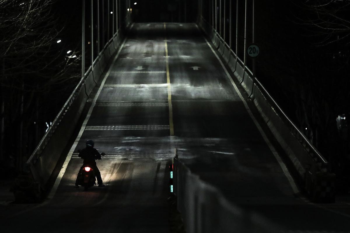 2020年2月16日,一人騎著電單車在武漢市的街道上。(Getty Images)