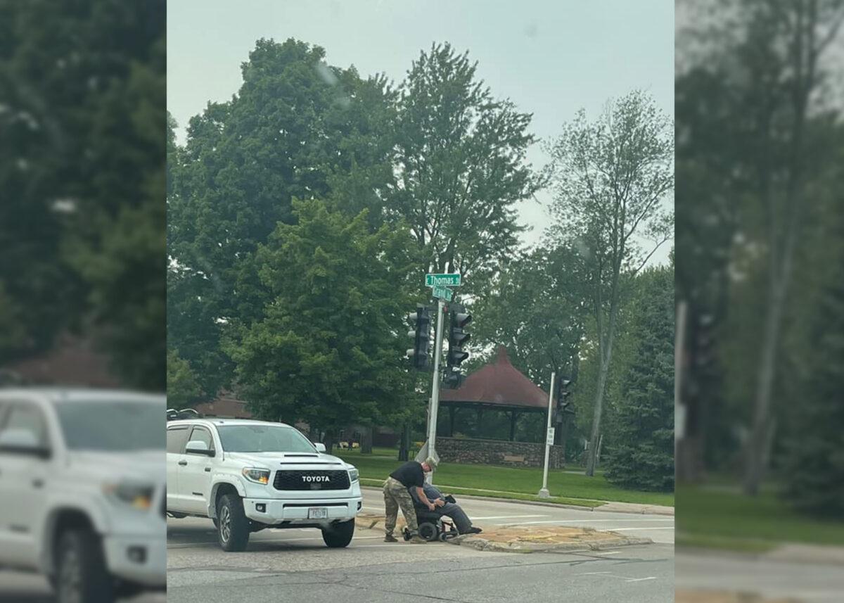 日前,美國一位年輕士兵熱心幫助一位坐輪椅的男子穿過一個繁忙的十字路口。(金伯利提供)