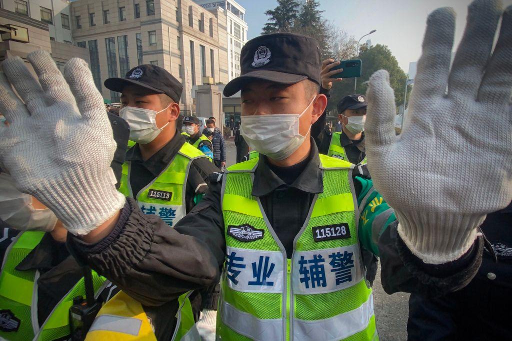 上海警方試圖阻止記者在浦東新區人民法院外錄製錄像。(Leo RAMIREZ/AFP)