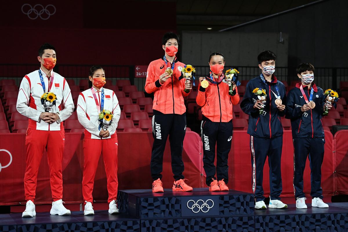 7月26日,在東京都體育館舉行的混合雙打乒乓球獎牌儀式上,金牌得主日本的水谷隼(左三)和日本的伊籐美誠(中間),銀牌得主中國的許昕(左)和中國的劉詩文,以及銅牌得主台灣的鄭一清(右)和台灣的林允珠。(JUNG Yeon-je / AFP)