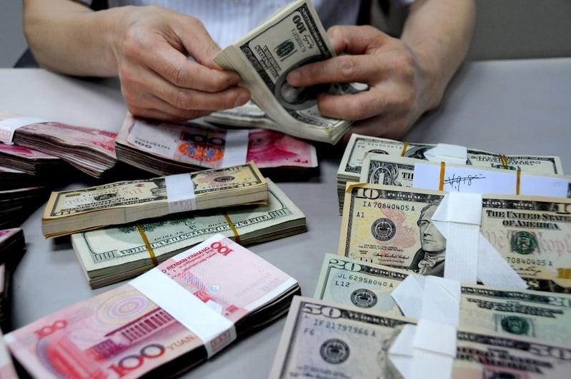 大陸多位財經評論學者核對官方數據,發現超過4000億美元的外匯儲備從官方數據中消失。圖為中國一銀行分支外匯部行員在點數錢幣。(Stringer: ChinaFotoPress / 2011 Getty Images)