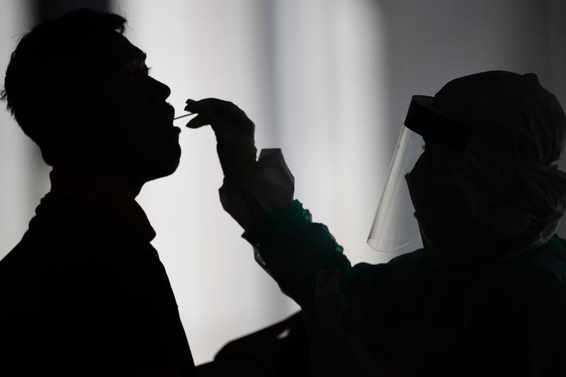 馬來西亞國家元首蘇丹阿布都拉2021年1月12日宣佈全國進入緊急狀態,以遏止疫情擴散。圖為示意圖。去年吉隆坡郊外Gombak,一名衛生工作人員使用藥籤從一名男子那裏收集一份樣本進行中共肺炎病毒檢測。(MOHD RASFAN/AFP via Getty Images)