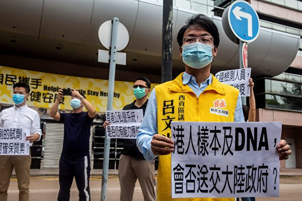 去年7月香港行政長官林鄭月娥將華大基因等大陸公司引入香港進行核酸檢測。圖為2020年8月2日,香港民眾在香港醫院管理局總部外舉牌,抗議特區政府讓大陸檢查人員在香港進行中共病毒檢測,擔心出現質量控制問題,以及DNA樣本可能被送給中共。(ISAAC LAWRENCE/AFP via Getty Images)