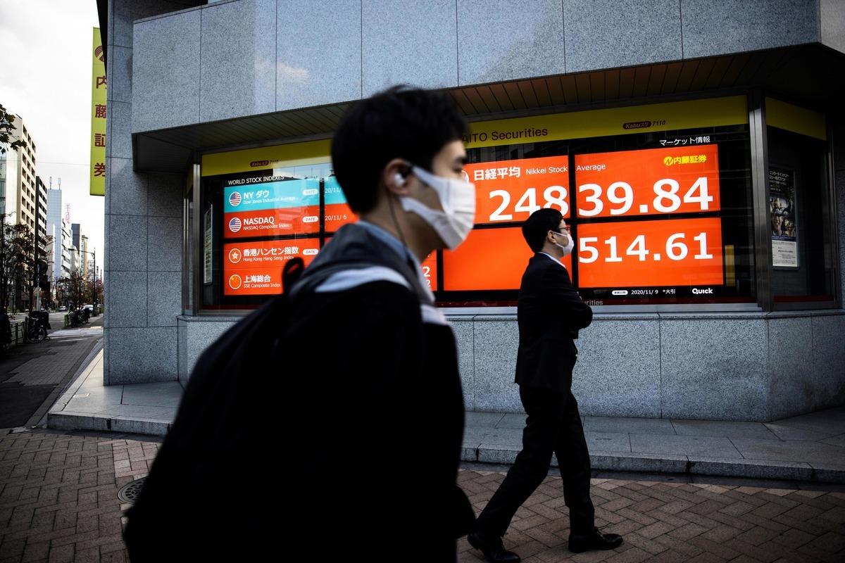 2020年11月9日,日本東京,兩名戴口罩的民眾路過電子看板。(BEHROUZ MEHRI/AFP via Getty Images)