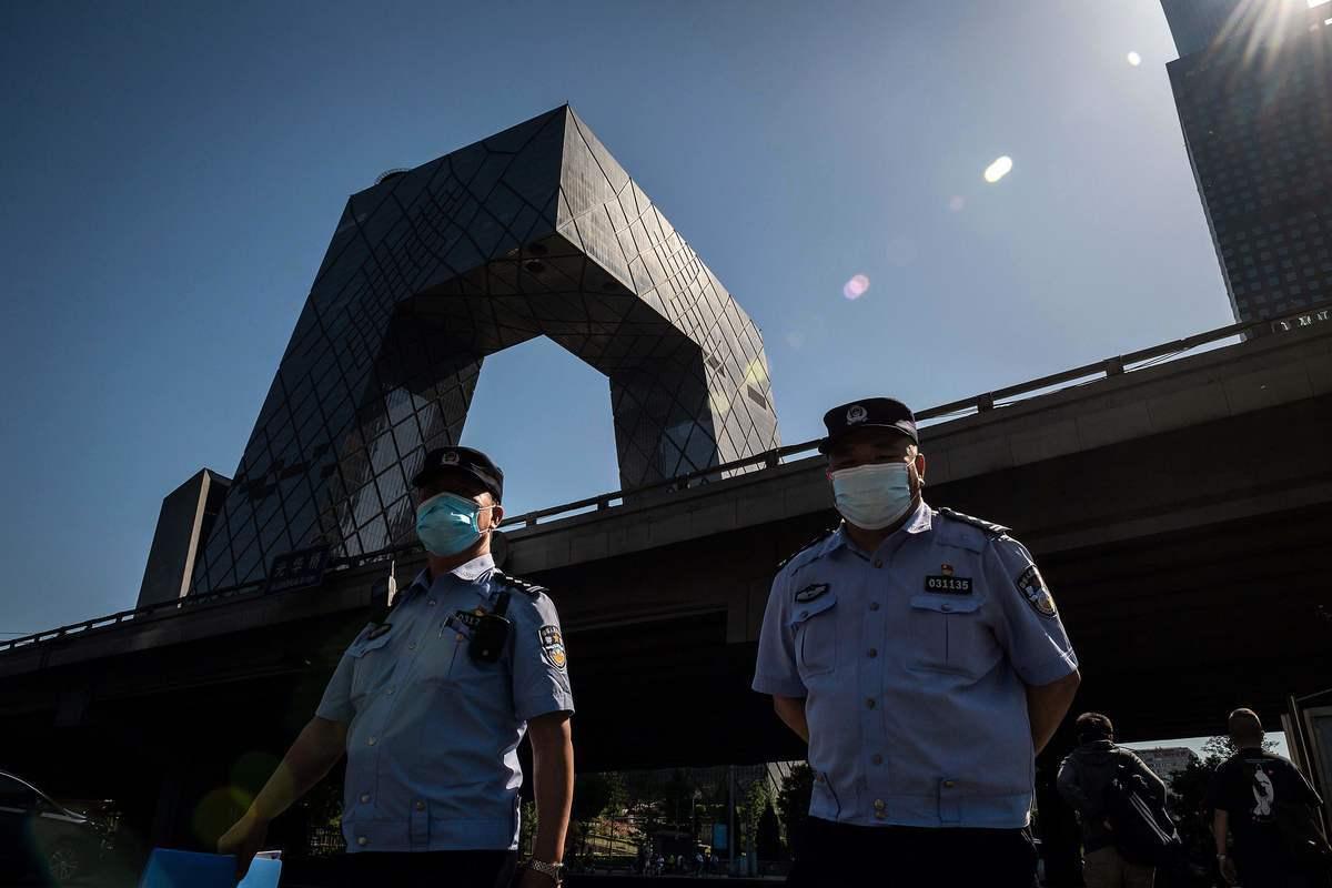 圖為戴著口罩的中共警察從央視大樓前走過。( NICOLAS ASFOURI/AFP via Getty Images)