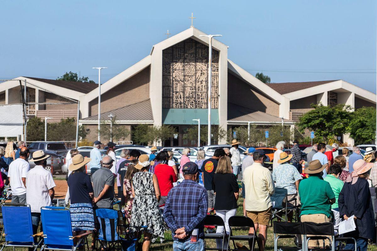 圖為2020年7月19日,人們戴著口罩在加州杭廷頓海灘的一座教堂外做禮拜。(APU GOMES/AFP via Getty Images)