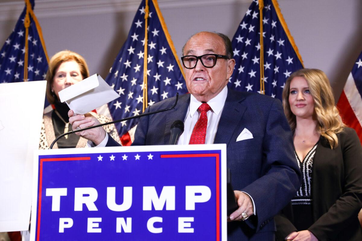 特朗普律師、前紐約市市長魯迪·朱利安尼(Rudy Giuliani)在特朗普競選高級法律顧問珍娜·埃利斯(Jenna Ellis,右)和律師西德尼·鮑威爾(Sidney Powell)在2020年11月19日的新聞發佈會上。(Charlotte Cuthbertson/The Epoch Times)