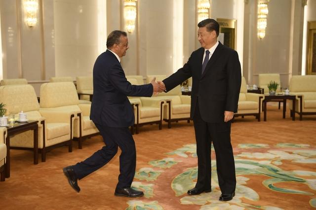 世界衛生組織秘書長譚德塞(左)與中國國家主席習近平(右)在北京會面。資料照。(AFP)