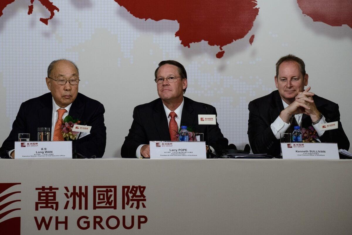 從左到右:萬洲國際董事長兼首席執行官萬隆(Wan Long),史密斯菲爾德首席執行官兼總裁拉里・波普(Larry Pope)和史密斯菲爾德首席財務官肯尼斯・蘇利文(Kenneth Sullivan)於2014年4月14日在香港舉行的新聞發佈會上。(PHILIPPE LOPEZ/AFP via Getty Images)