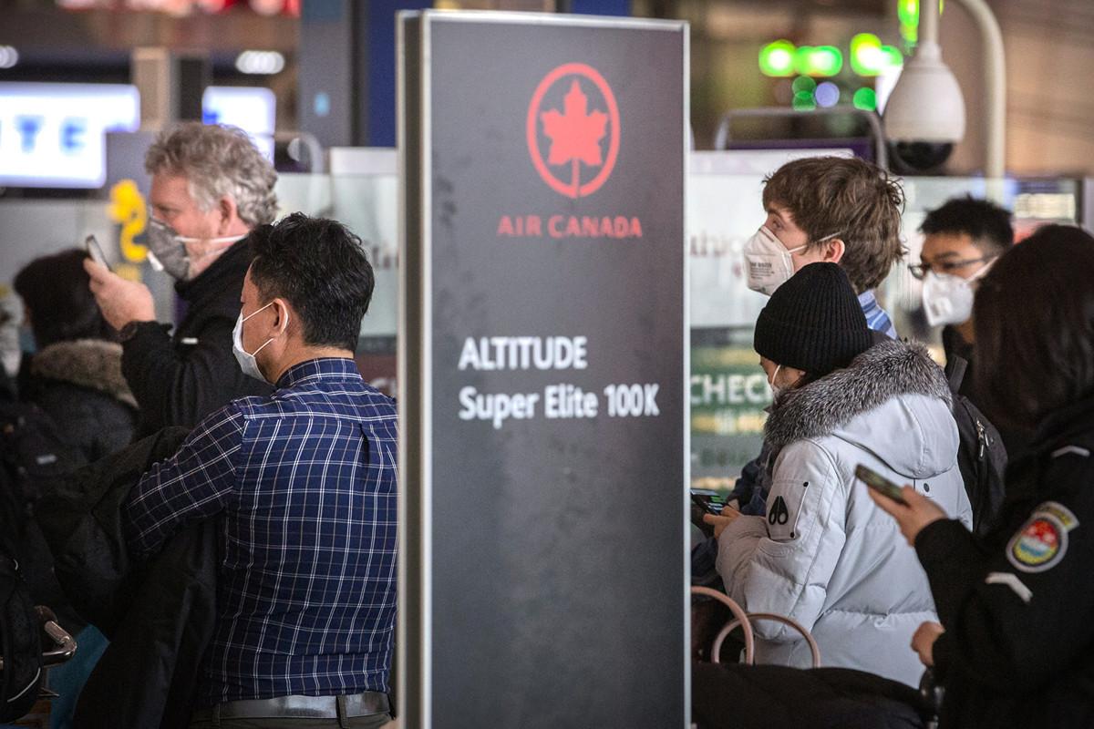 1月30日,北京首都國際機場,在加航值機櫃檯前,人們載著口罩排隊辦理乘機手續。(加通社)