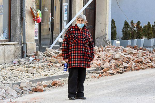 2020年12月29日,克羅地亞彼得里尼亞(Petrinja),該鎮遭受6.4級地震襲擊後,一位鎮民站在受損的房屋旁。(DENIS LOVROVIC/AFP via Getty Images)