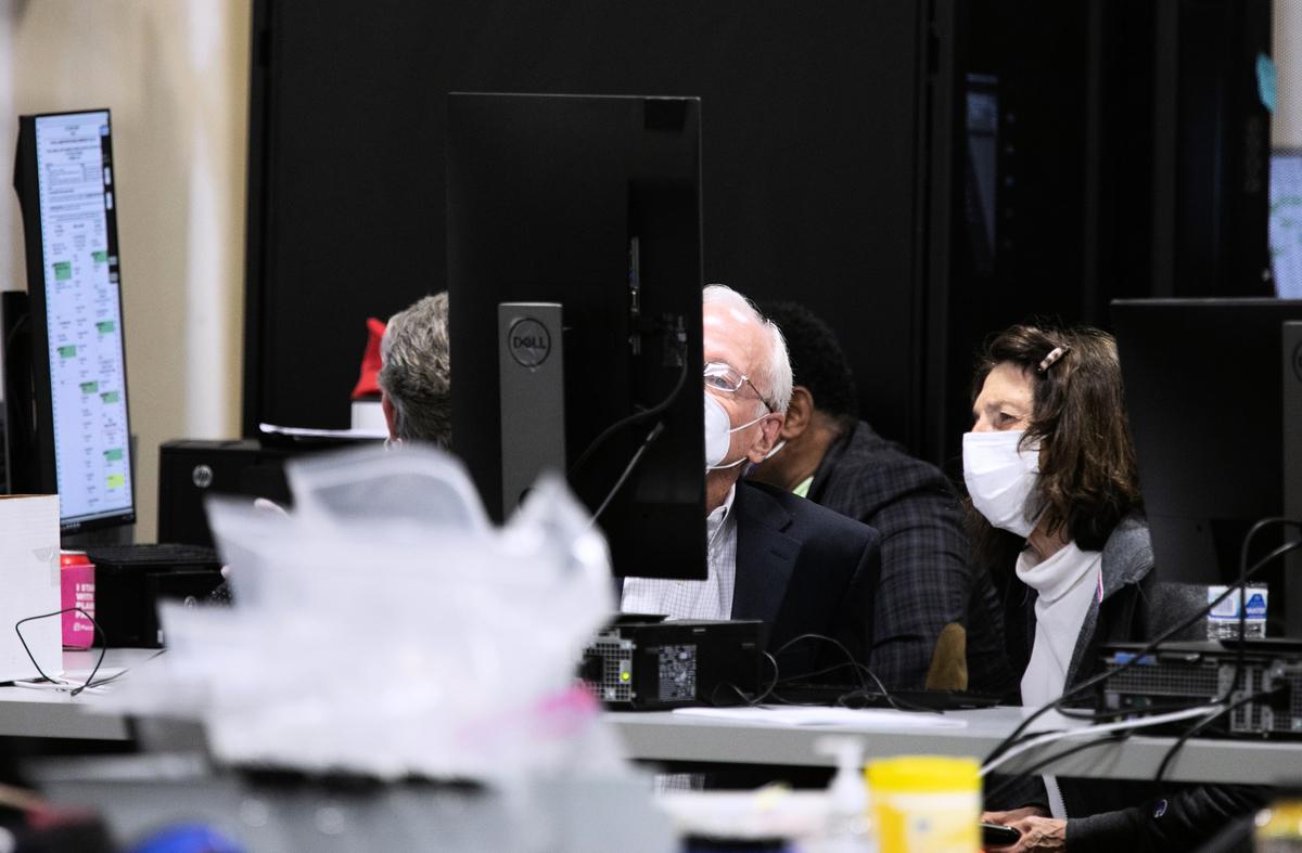 2020年11月4日,在佐治亞州的亞特蘭大,裁決複審小組的成員正在看富爾頓縣選舉準備中心掃瞄的缺席選票。(Jessica McGowan/Getty Images)
