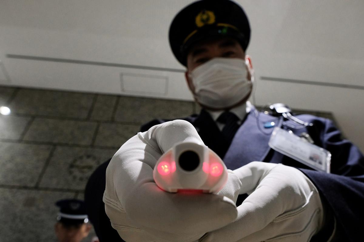 日本宣佈對中國及南韓旅客採取最嚴格的邊境管制措施,以防止中共病毒擴散。圖為東京市政廳保安2020年3月5日測量訪客體溫。(Kazuhiro NOGI/AFP)