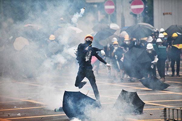 2019年7月27日,香港民眾來到元朗集會,抗議警察暴力執法。圖為一青年把警察發射的催淚彈扔回去。(ANTHONY WALLACE/AFP/Getty Images)