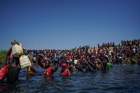 2021年9月19日,海地移民聚集在德州德爾里奧市國際大橋附近,成為一個不斷膨脹的邊境危機。(PAUL RATJE/AFP via Getty Images)