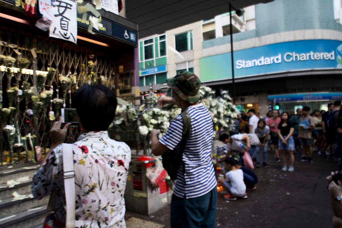 事發近20天,仍然關閉的太子站B出口處擺滿了白色鮮花。18歲的John(圖中戴帽子的男孩),站在太子站封閉閘門前默默地撒著紙錢。他不相信警方的「沒人被打死」之說。(駱亞/大紀元)