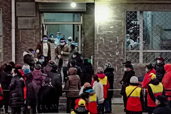 圖為2020年12月22日,遼寧省大連市居民等待接受核酸檢測。(STR/AFP via Getty Images)